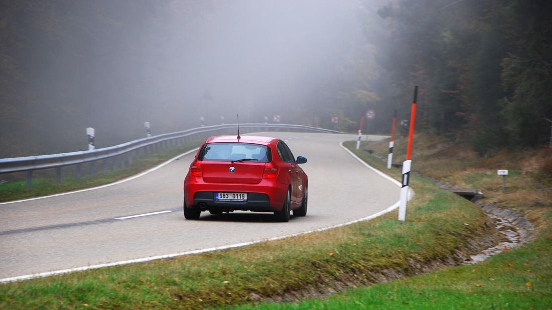 červené BMW řady 1 na silnici v lese v oblasti Schwarzwald