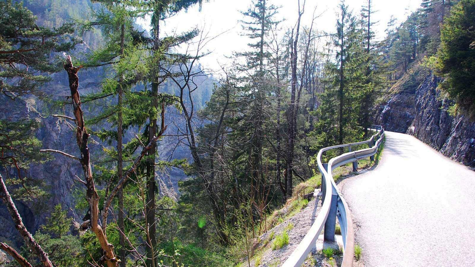 Úzká silnice lesem nad propastí