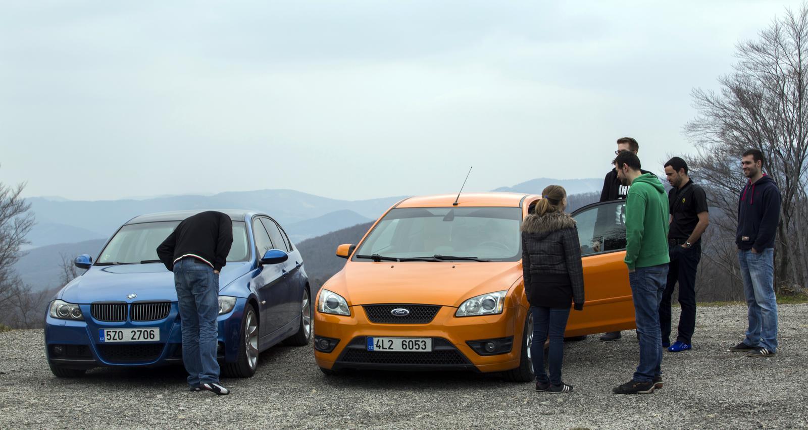BMW 330i a Ford Focus ST a skupinka debatujících lidí