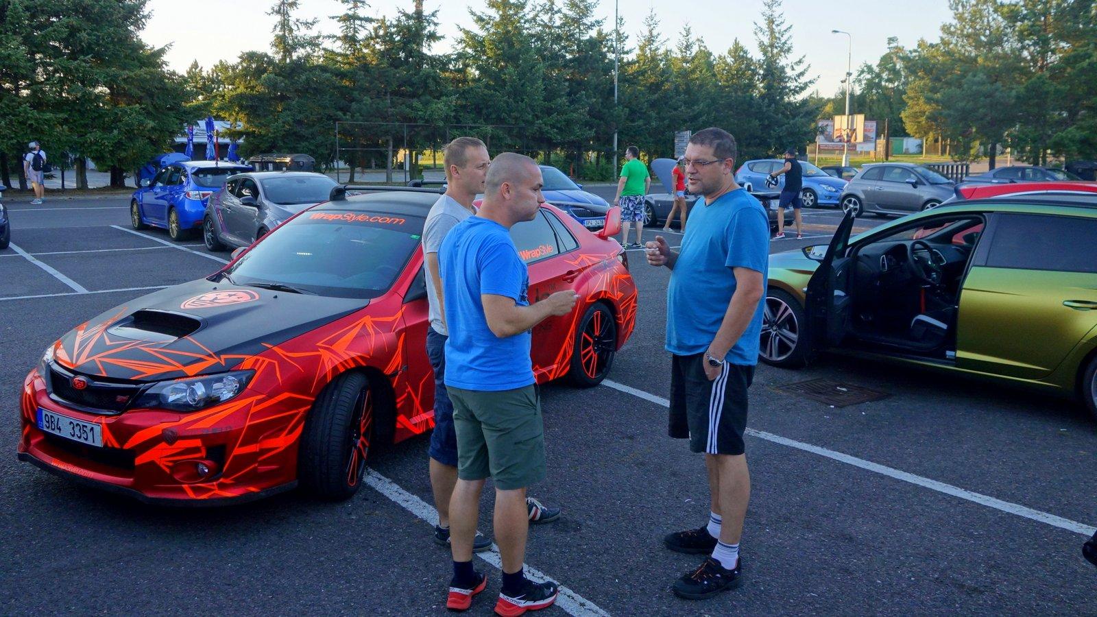 lidi si povídají u aut na parkovišti